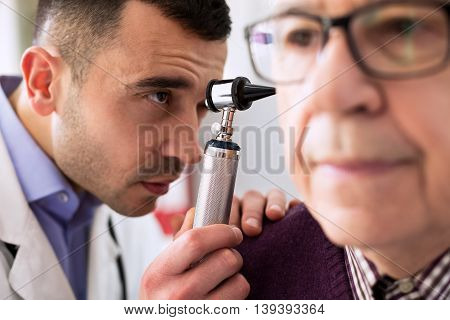 Otologist examining senior patient ear, close up