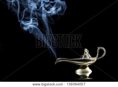 Magic lamp on black background from the story of Aladdin with Genie appearing in blue smoke concept for wishing, luck and magic.