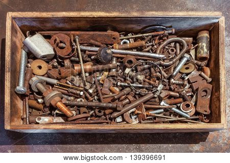 Wooden box with bolts screws nuts bearings valves washers nails on the metal background