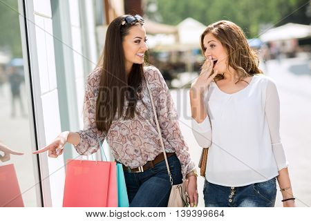 Surprised Women Looking And Pointing To The Store