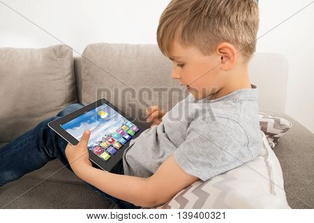 Boy Using Digital Tablet With Multicolored Apps On It