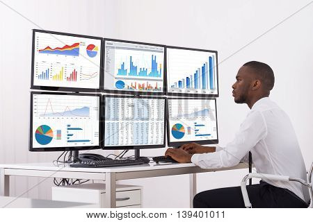 Young Businessman Analyzing Graph On Multiple Computers In Office