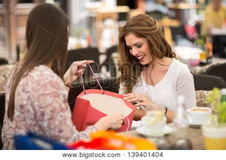 Woman shows to her friend what she bought in store