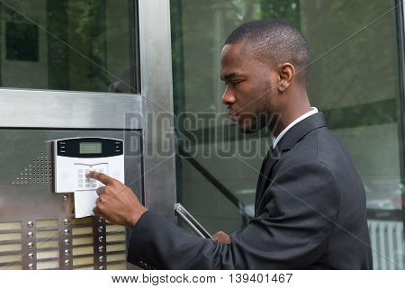 Young African Businessman Entering Code In Security System