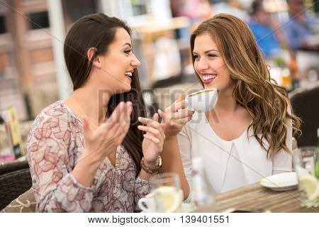 Cheerful young friends having fun in a cafe coffee time