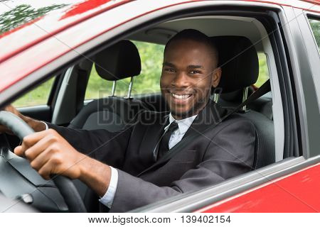 Portrait Of A Happy Young African Businessman Driving Car