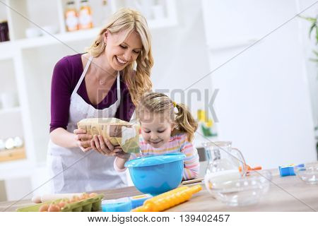 Smiling Beautiful Mom With Child Putting Flour