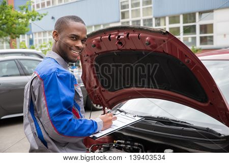 Young African Mechanic Writing On Clipboard In Front Of Open Car Engine