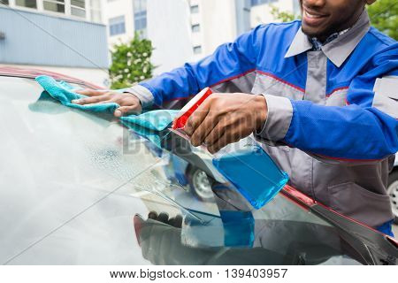 Young Male Worker Cleaning Car Windshield With Cloth And Spray