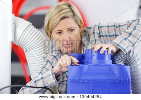 female electrician performing work on machine