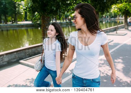 Mother and daughter running skipping along the shore