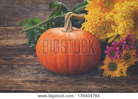 one orange pumpkin with mum flowers on wooden textured table, retro toned