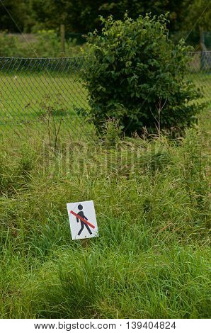 pictogram sign in grass area. Daylight cloudy.