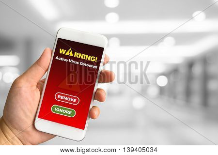 Woman hand holding smartphone against white grey bokeh abstract background Virus Alert concept