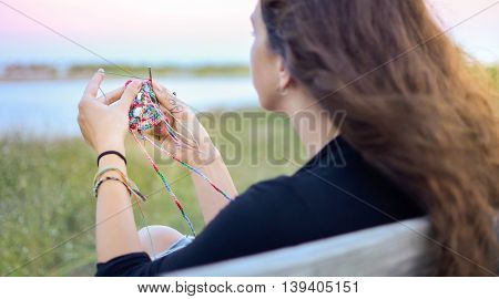 Woman Crocheting By The Lake
