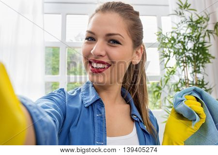 Beautiful Young Woman Taking A Selfie While Cleaning Home