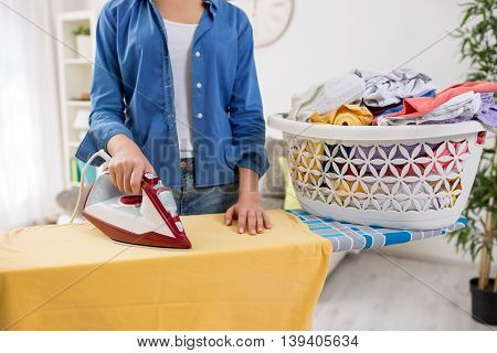Beautiful young woman ironing blouse on ironing board