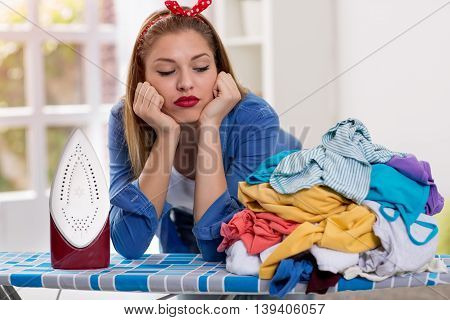 Lazy young woman looks at laundry on ironing board