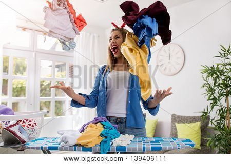 Aggressive frustrated young woman throws laundry in the air