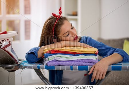 Tired young woman sleeping on the ironed laundry at home