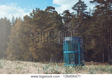 Concept Eco friendly, ecology theme. Green dustbins outside, black plastic garbage bags on nature background. Summer or autumn forest, tree, grass and leaves near road in countryside. Copy space, text place.