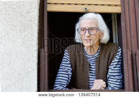 Old And Lonely Lady Looking Outside Through Window