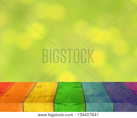 table from multicolored wooden boards with blurred green natural background