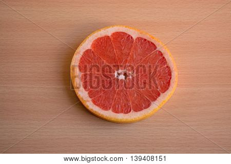One slice of red grapefruit on a wooden background