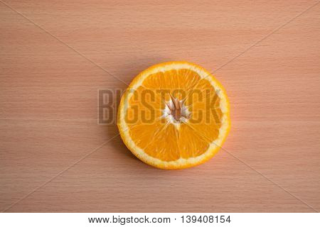 One slice of orange on a wooden background