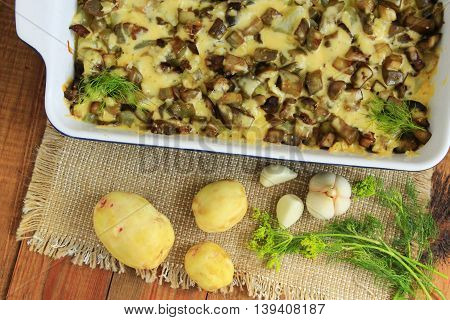 Baked potato with slices of eggplant cheese and garlic. New potatoes garlic and fennel on the table. Top view