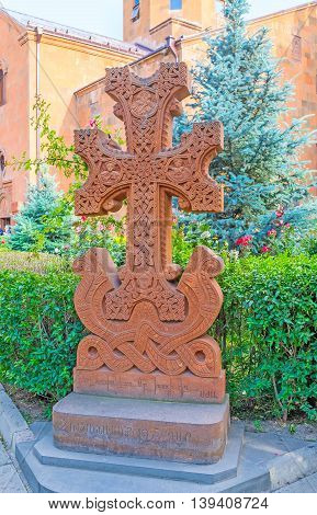 YEREVAN ARMENIA - MAY 29 2016: The red tuff Khachkar carved with patterns and inscriptions located in the courtyard of St John the Baptist Church on May 29 in Yerevan.