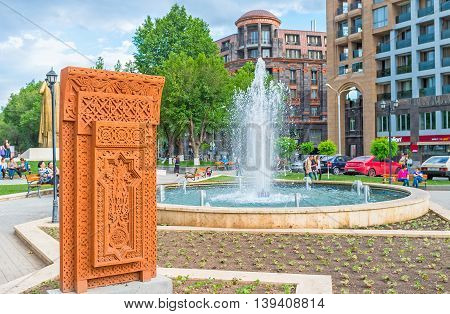 YEREVAN ARMENIA - MAY 29 2016: The bright orange Khachkar with the complex carved pattern in the open air exhibition named The Cultural Genocide: symbol of Khachkars on May 29 in Yerevan.