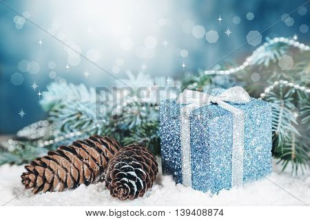 The composition of the winter holidays in the snow with a gift cones, fir branches, decorations