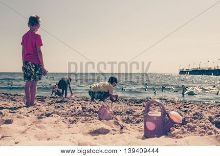 Joyful active childhood. Playful kids playing near water on seaside. Children having fun on summer beach. Young tourists spending actively time.
