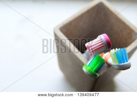 Shallow Dof Shot Of Three Toothbrushes In A Clay Tumbler In The Morning Light