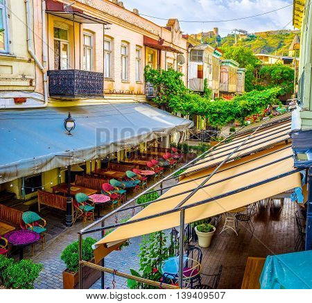 TBILISI GEORGIA - MAY 28 2016: The beautiful taverns' terraces are protected with canopies producing the shade to the guests on May 28 in Tbilisi.