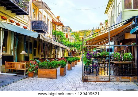 TBILISI GEORGIA - MAY 28 2016: The cozy terraces of the restaurants surrounded by flowers and plants in pots on May 28 in Tbilisi.