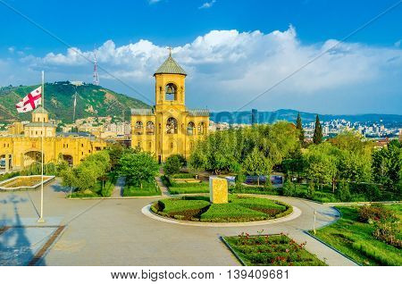 The Sameba Cathedral boasts beautiful garden. with colorful flower beds and trimmed bushes Tbilisi Georgia.