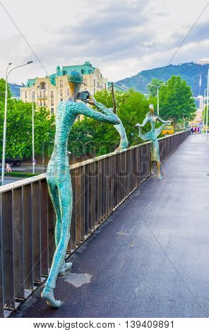 TBILISI GEORGIA - MAY 28 2016: The couple of bronze lovers - Ali and Nino on Baratashvili Bridge makes photos of each other on May 28 in Tbilisi.