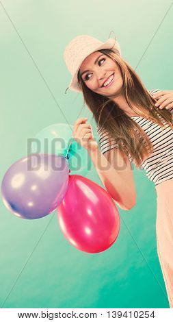 Happiness and fun. Summer time. Young attractive happy woman in straw hat with colorful balloons over green background.
