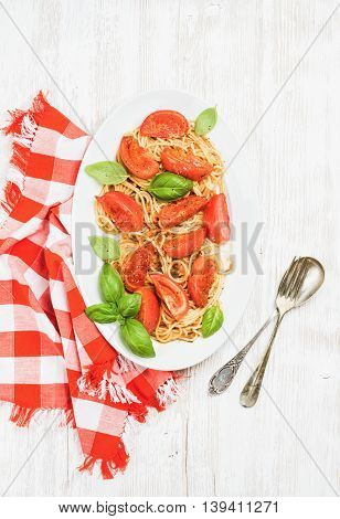 Pasta dinner. Spaghetti with roasted tomatoes and fresh basil in oval dish over white wooden background, top view, vertical composition