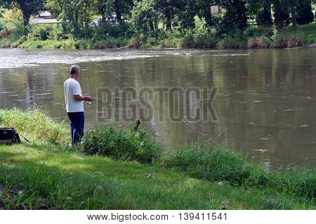 SHOREWOOD, ILLINOIS / UNITED STATES - AUGUST 30, 2015: A man fishes from the shore of the Du Page River in Shorewood.
