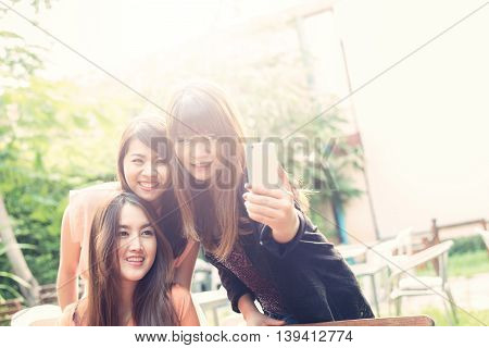 Three beautiful happy Asian girl taking photo with smartphone.Image with sunlight filter.