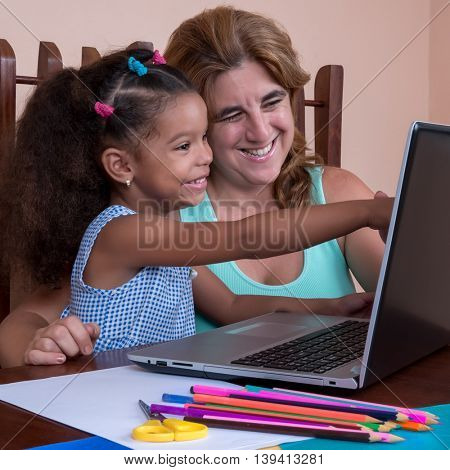 Small multiracial girl and her mother working on a laptop computer or surfing the internet together