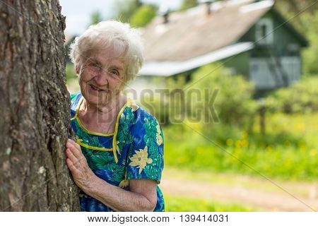 Grandmother looks out from behind a tree near his home.