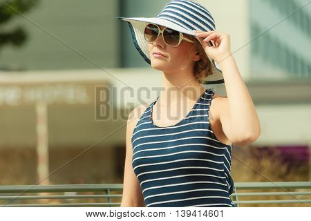 Fashion young woman in striped hat and dress sitting on bench outdoor. Pretty gorgeous girl relaxing enjoying summer vacation in city.