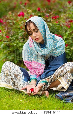 Sad indian woman sits on grass in garden in bright sari and holds petal
