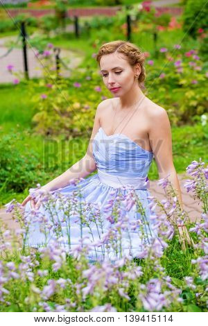 Pretty woman in long blue dress poses near flowers in summer garden