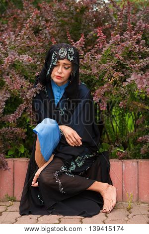 Sad woman in black sari sitting at border under bushes of barberry in park