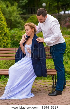 Pretty woman sits on bench, man puts his jacket for girl in green summer park